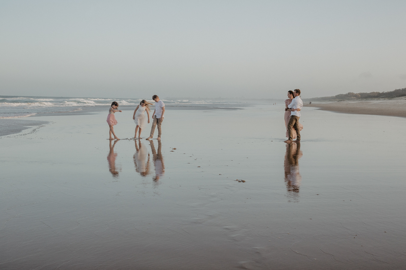family on a wurtulla beach on the sunshine coast. they are putting their feet in the water